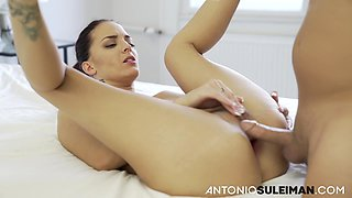 Naked brunette is holding her legs lifted high and rubbing her clit while getting assfucked