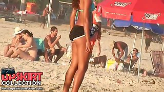 The turning on brunette on the beach is wearing the sport