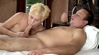 Blonde grandmother is being sexual treated by the young stud