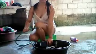 Asian girl doing laundry outdoors and teasing on webcam
