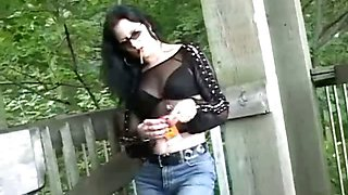 Brunette slut wearing fishnet shirt smoking sexy at the
